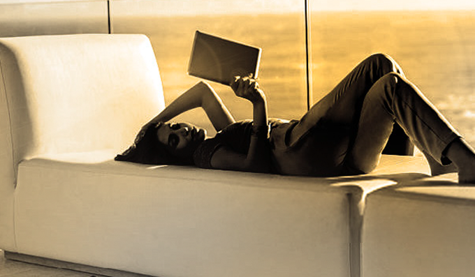 Woman lying on a sofa beside window reading magazine