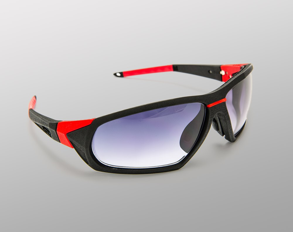Heavy eyeglasses frames with red detailing on grey background