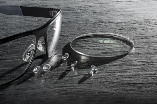 Black and white image of eyeglasses and lens on a table