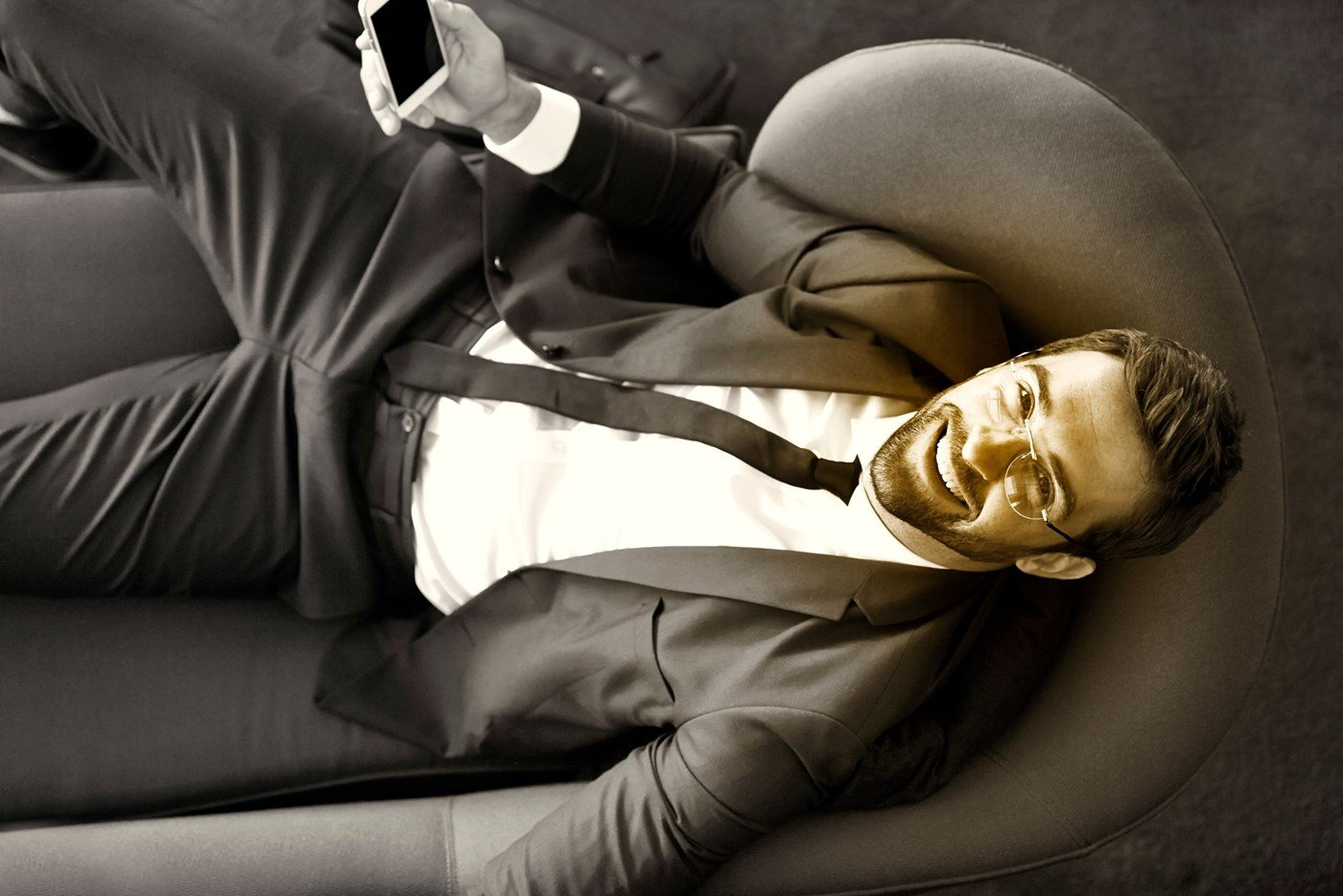 Male wearing eyeglasses sitting on sofa looking up at the camera with smartphone in right hand