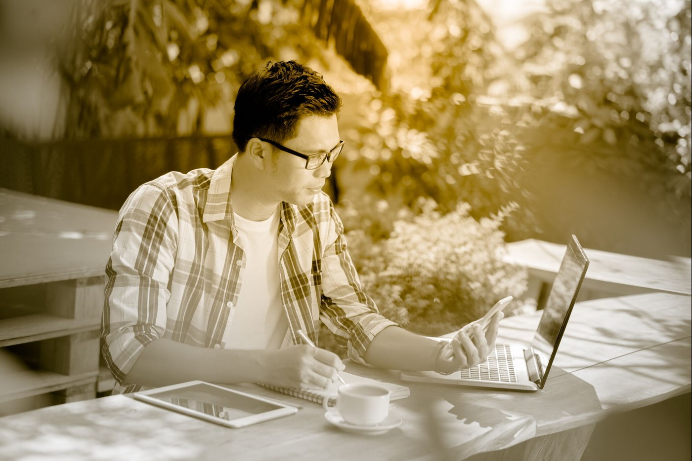 Male working outdoors on mobile and laptop wearing eyeglasses