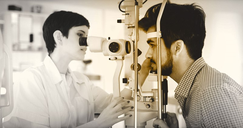 Female optician conducting eye examination on a male
