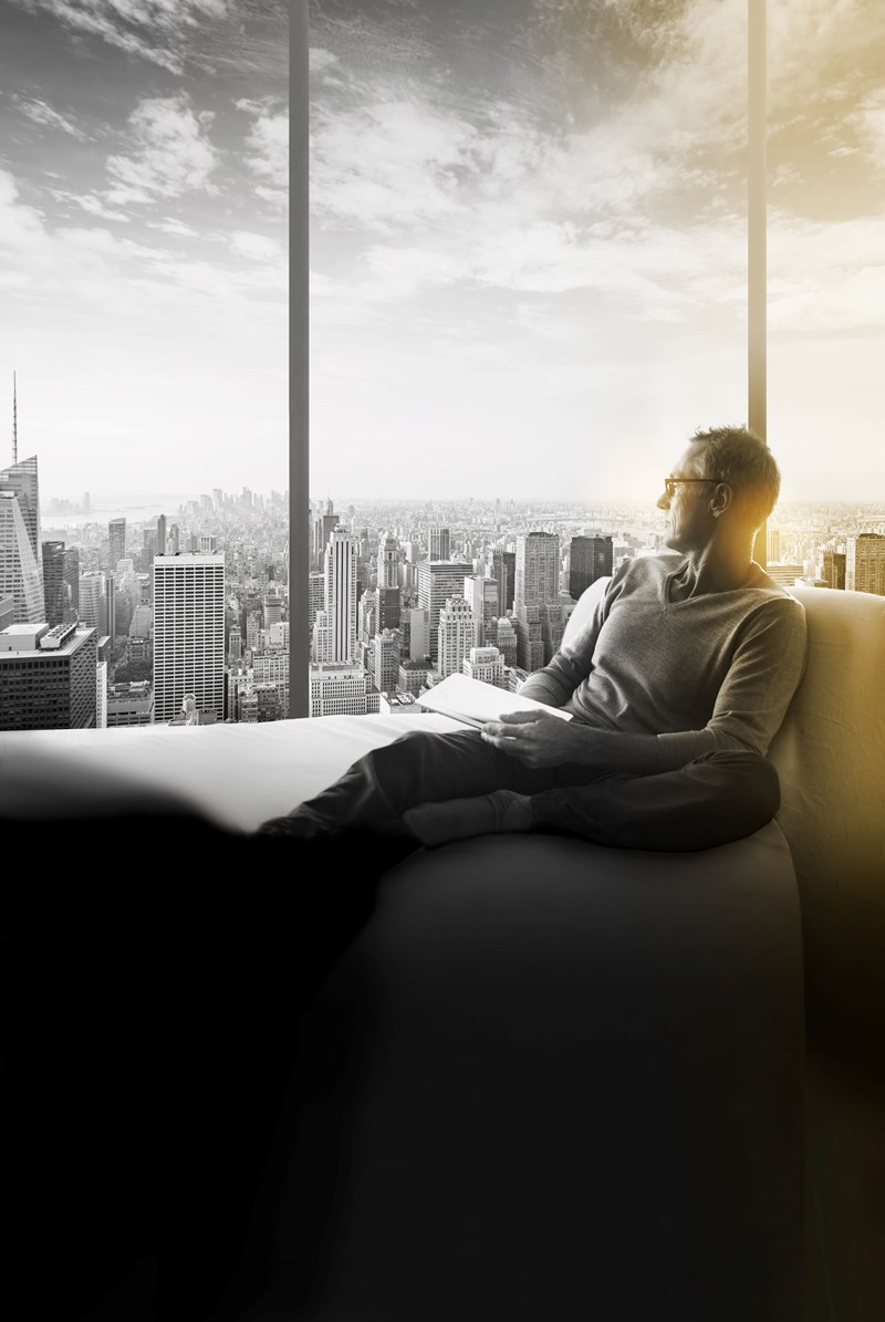 Male wearing eye glasses sitting on sofa looking out of skyscraper window
