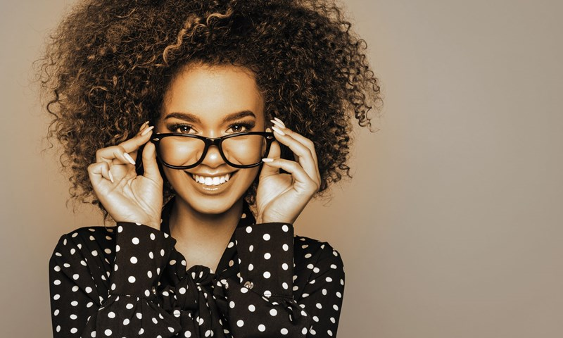 Female in spotted top smiling at camera trying on glasses