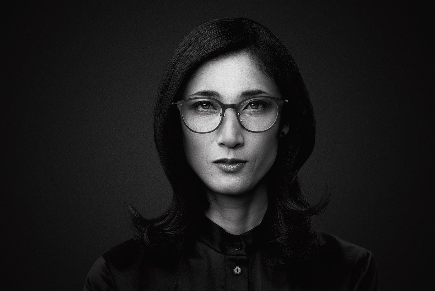 Black and white image of female wearing eyeglasses staring at the camera