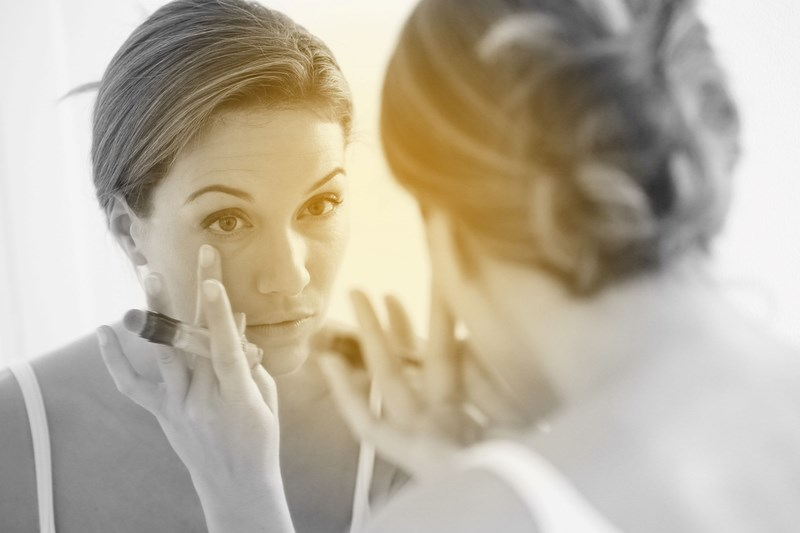 Woman applying concealer with her finger in a mirror