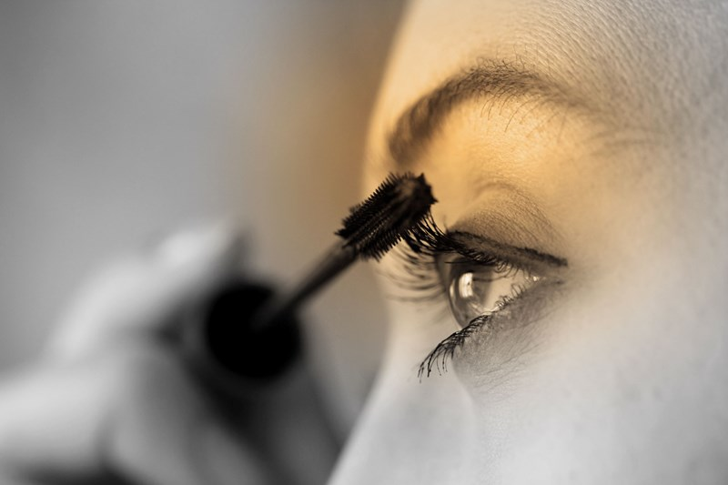 Female applying mascara on her left eye