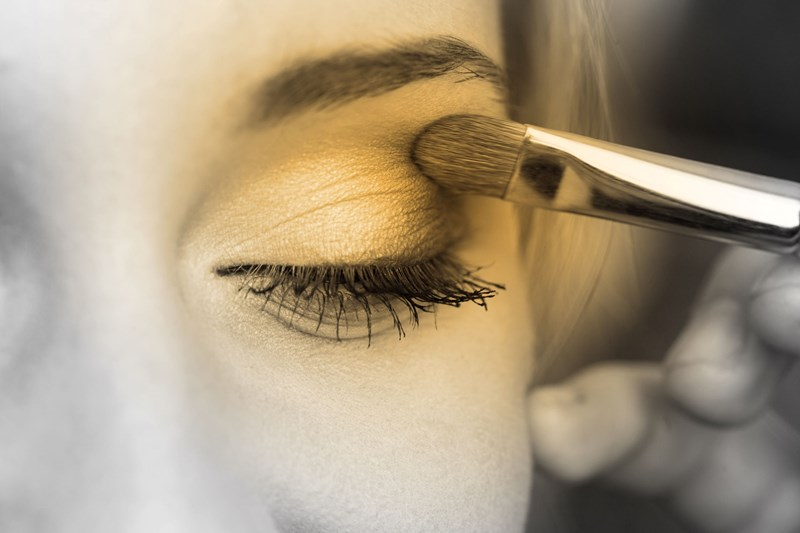 Female applying eyeshadow on her left eye