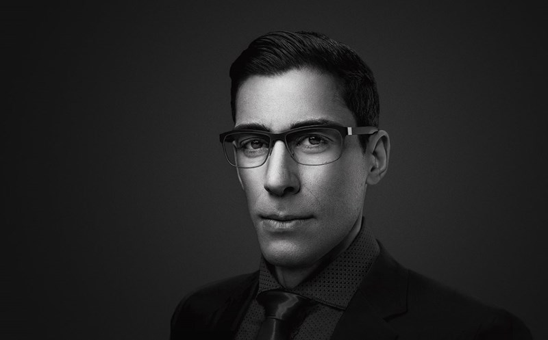 Black and white image of male wearing eyeglasses staring at the camera