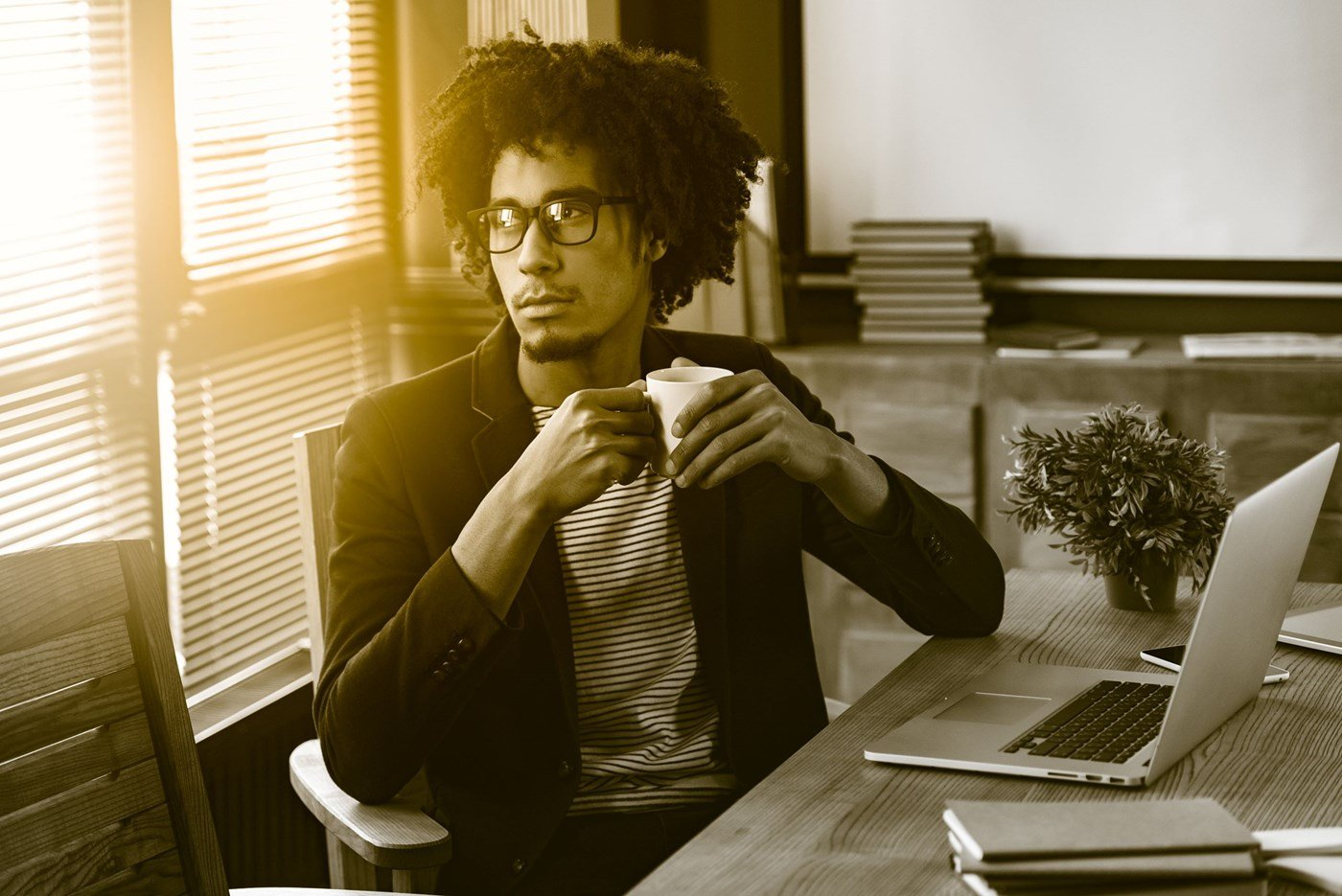 Male wearing eyeglasses in an office holding a coffee cup looking out of window