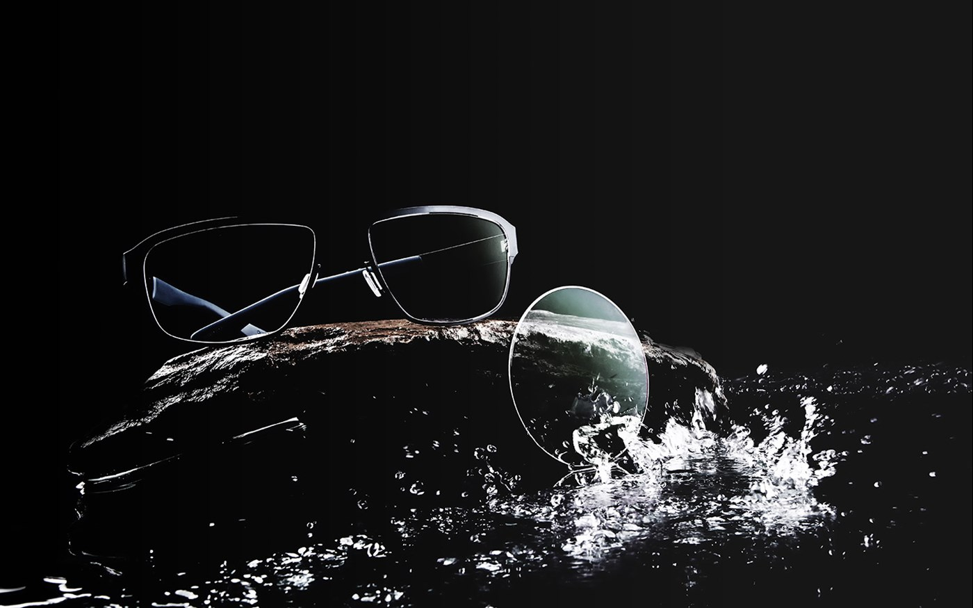 Eyeglasses and lens being splashed with water on a black background