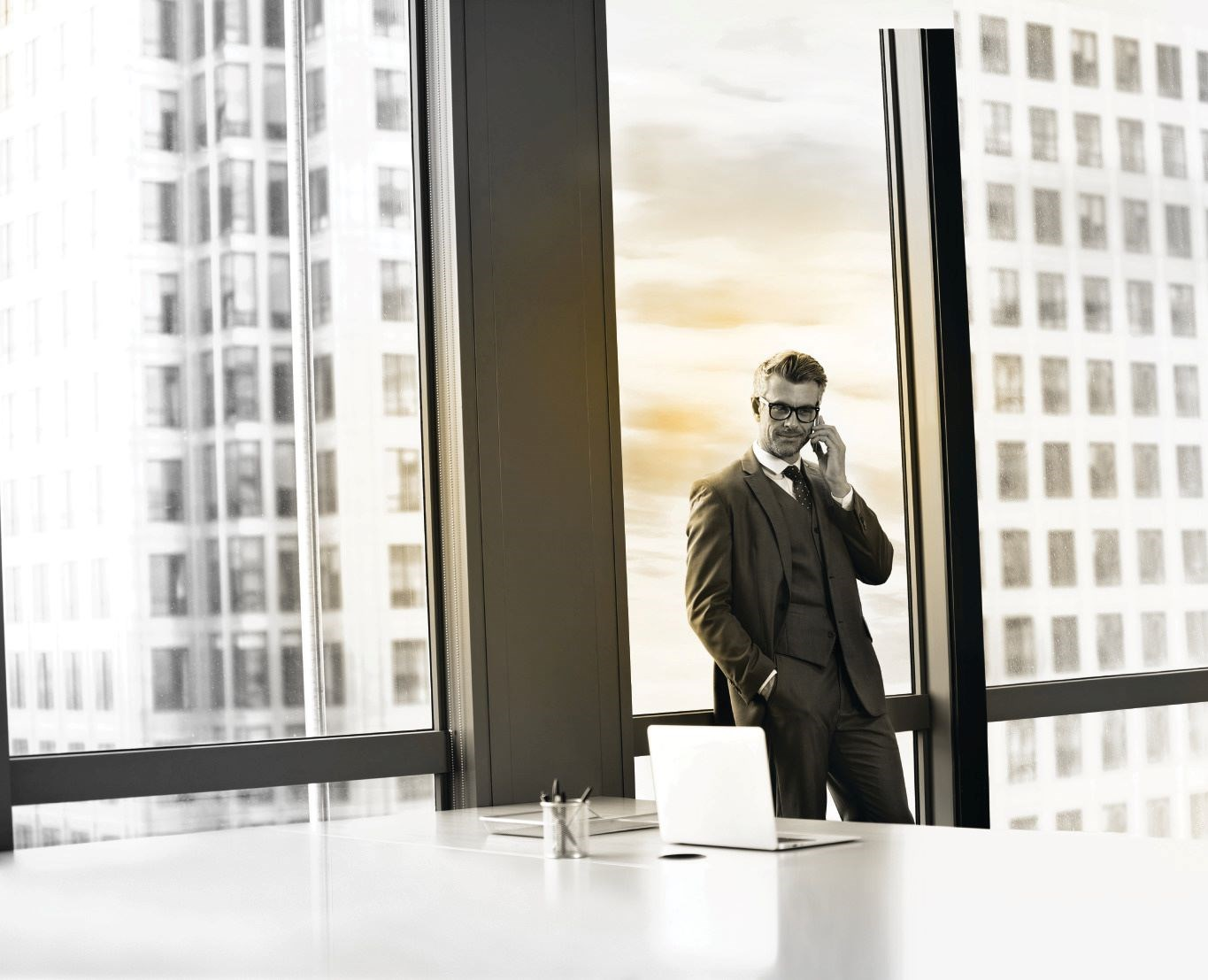 Male businessman wearing glasses on phonecall in office