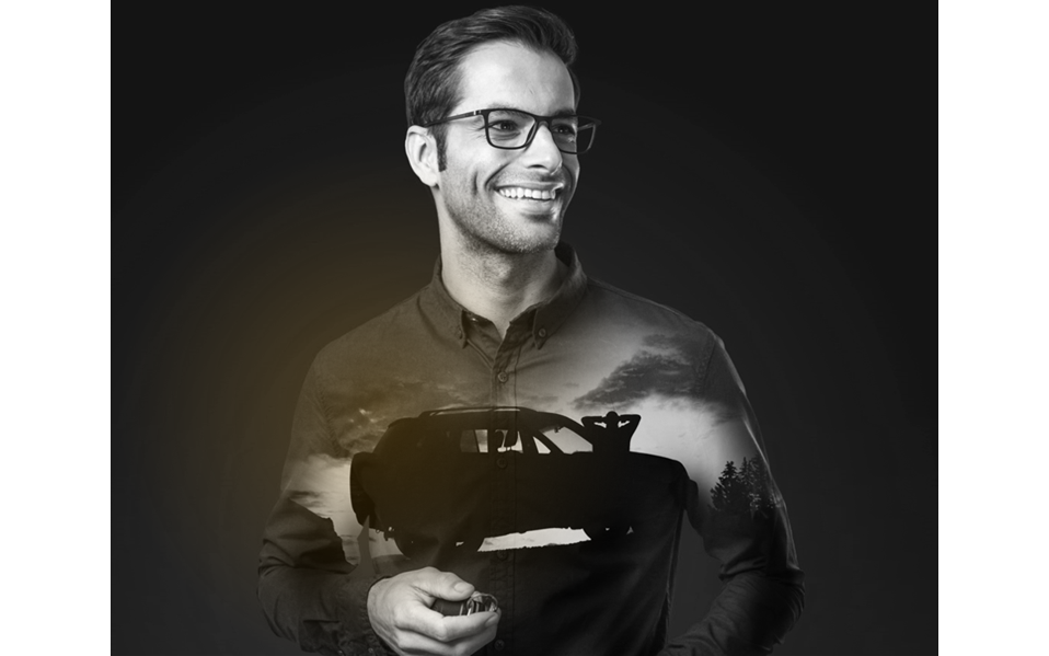 Male wearing eyeglasses smiling looking away from the camera with reflection of jeep on his tshirt