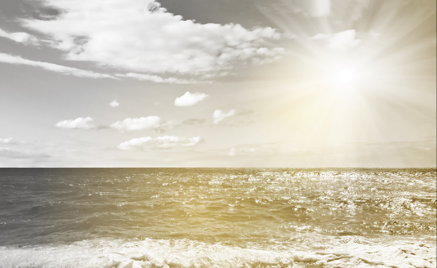 Image on a beach with the sea waves and the sun glaring down