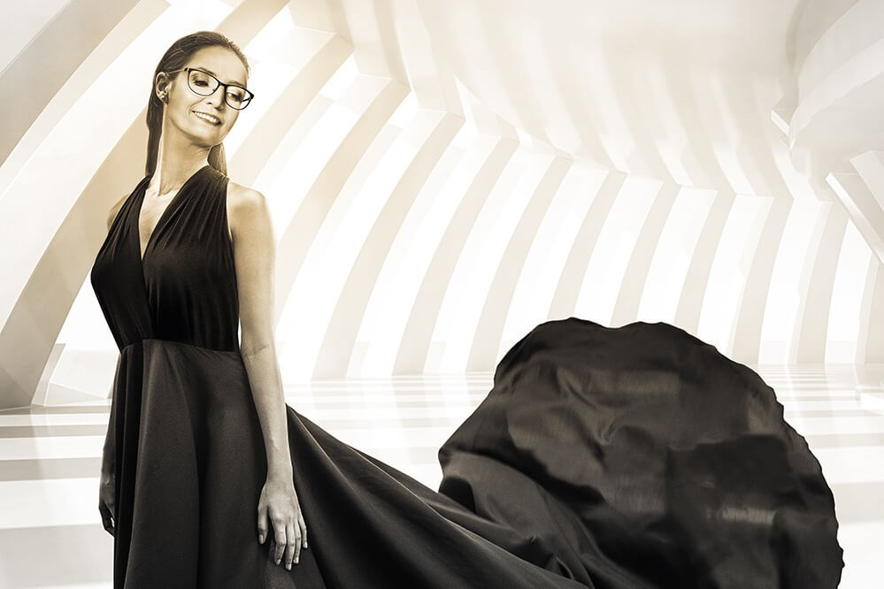 Female in black evening gown wearing glasses on bright backround