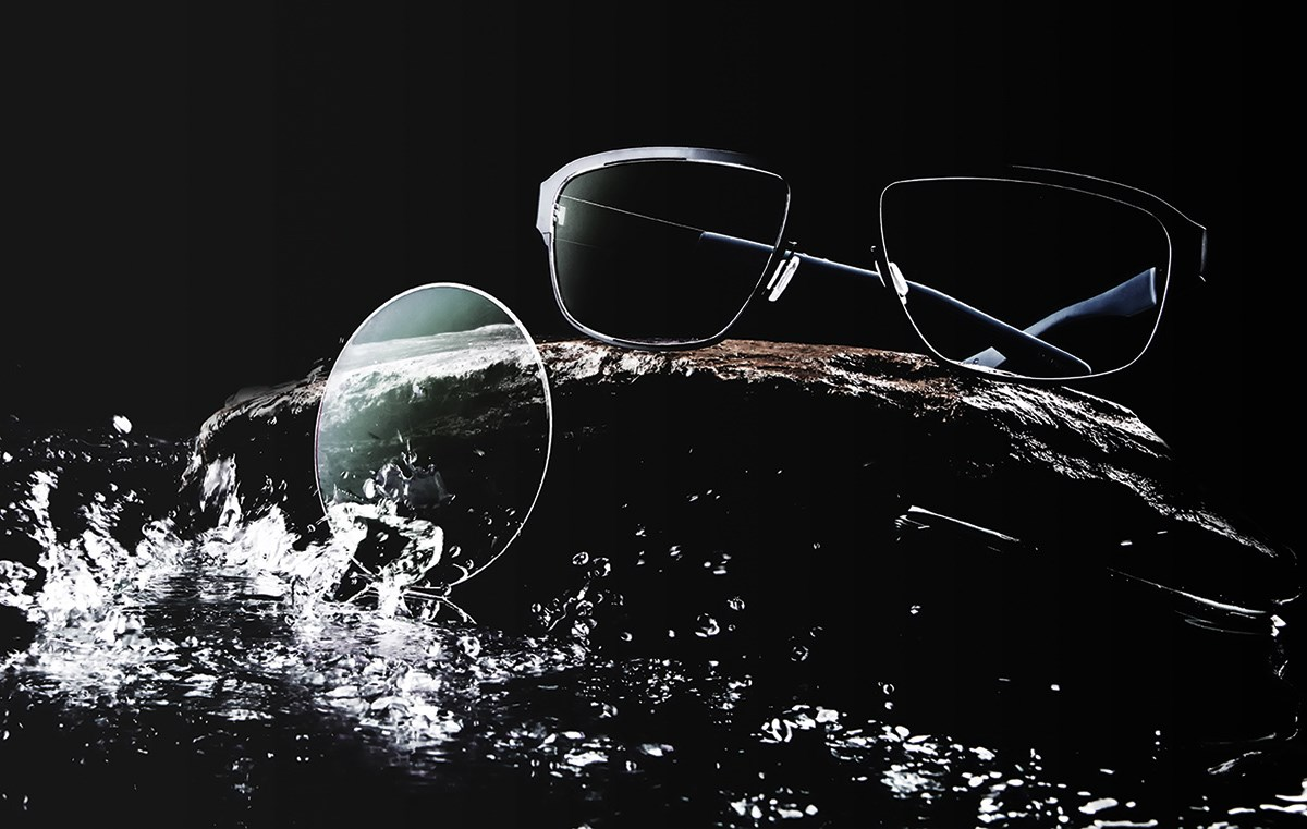 Glasses and lens on counter being splashed with water