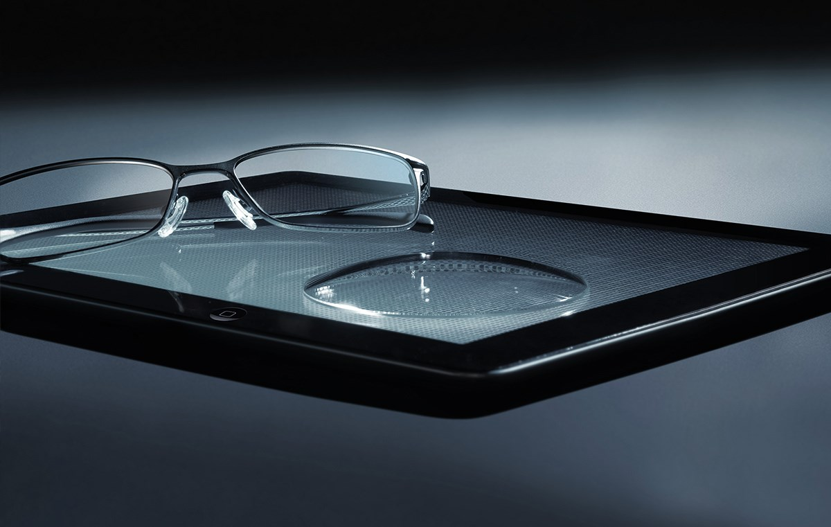 Eyeglasses sat on a tablet with lens