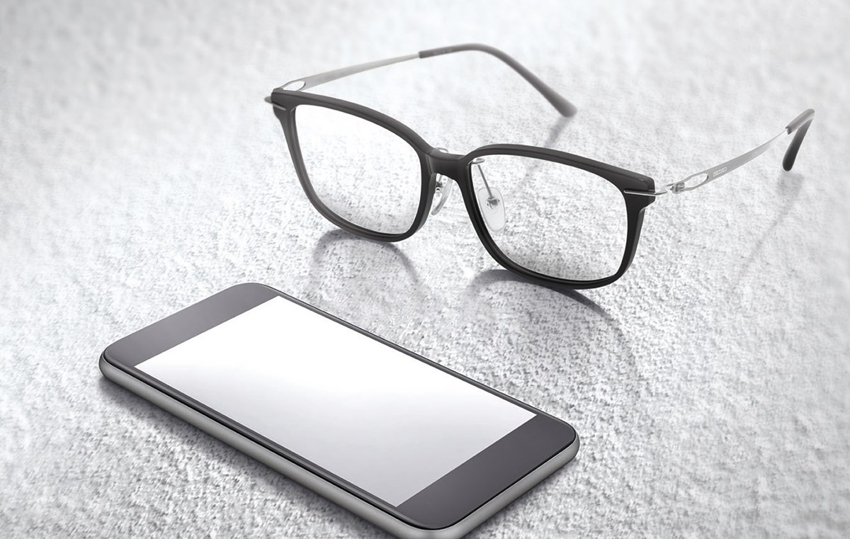 Spectacles sat on surface beside smartphone