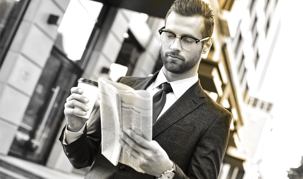 Male wearing glasses holding a coffee and reading a newspaper