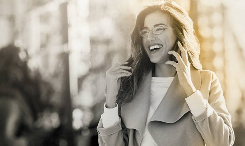 Female wearing eyeglasses on phone call smiling