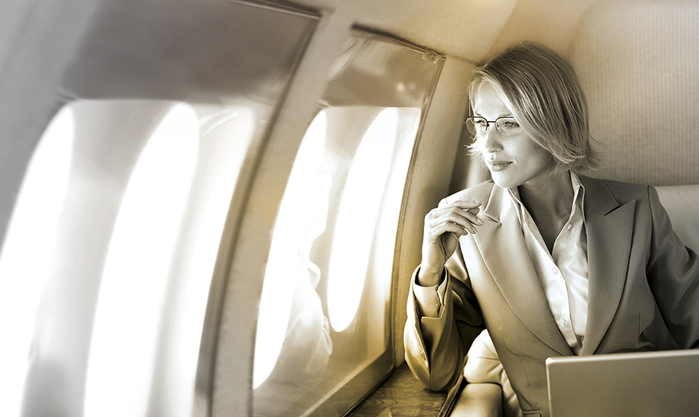 Female on flight wearing eyeglasses looking out of window with laptop in front of her