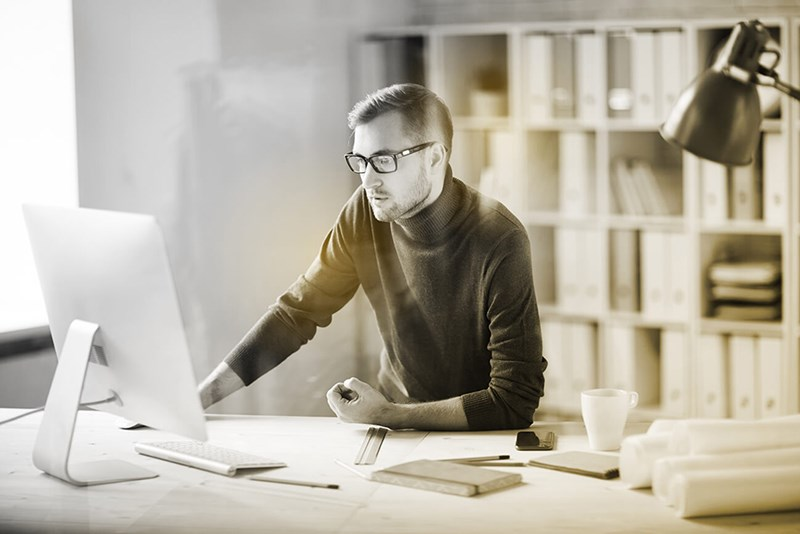 Male working indoors wearing eyeglasses behind computer screen