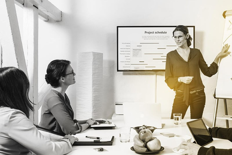 Female standing at front of boardroom taking a business meeting