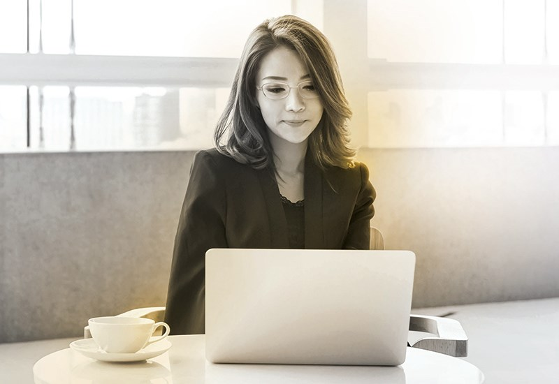 Female wearing glasses sat behind laptop