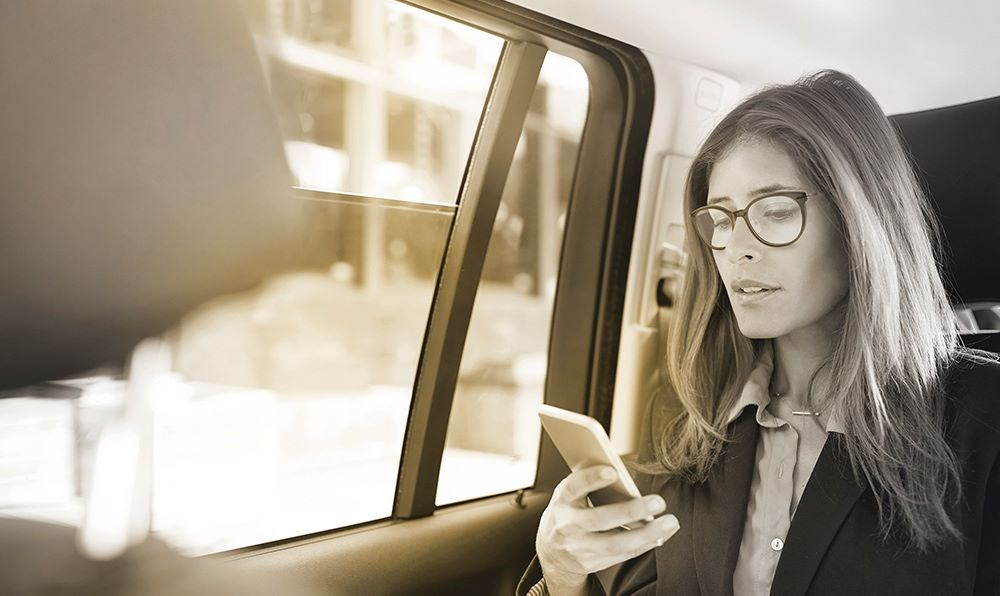 Female in back seat of car wearing glasses using smartphone