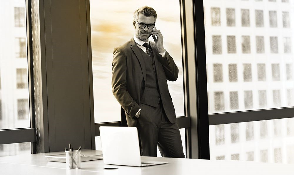 Business man in suit wearing glasses standing behind desk on a phone call