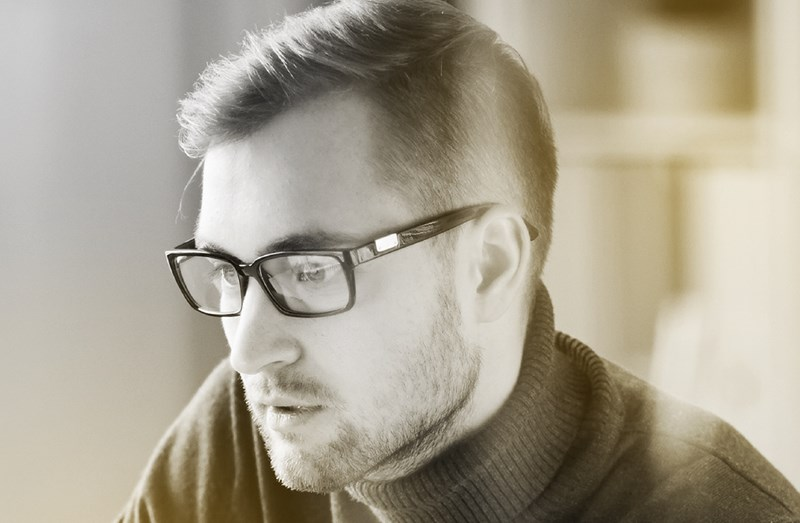 Male wearing eyeglasses focused on something