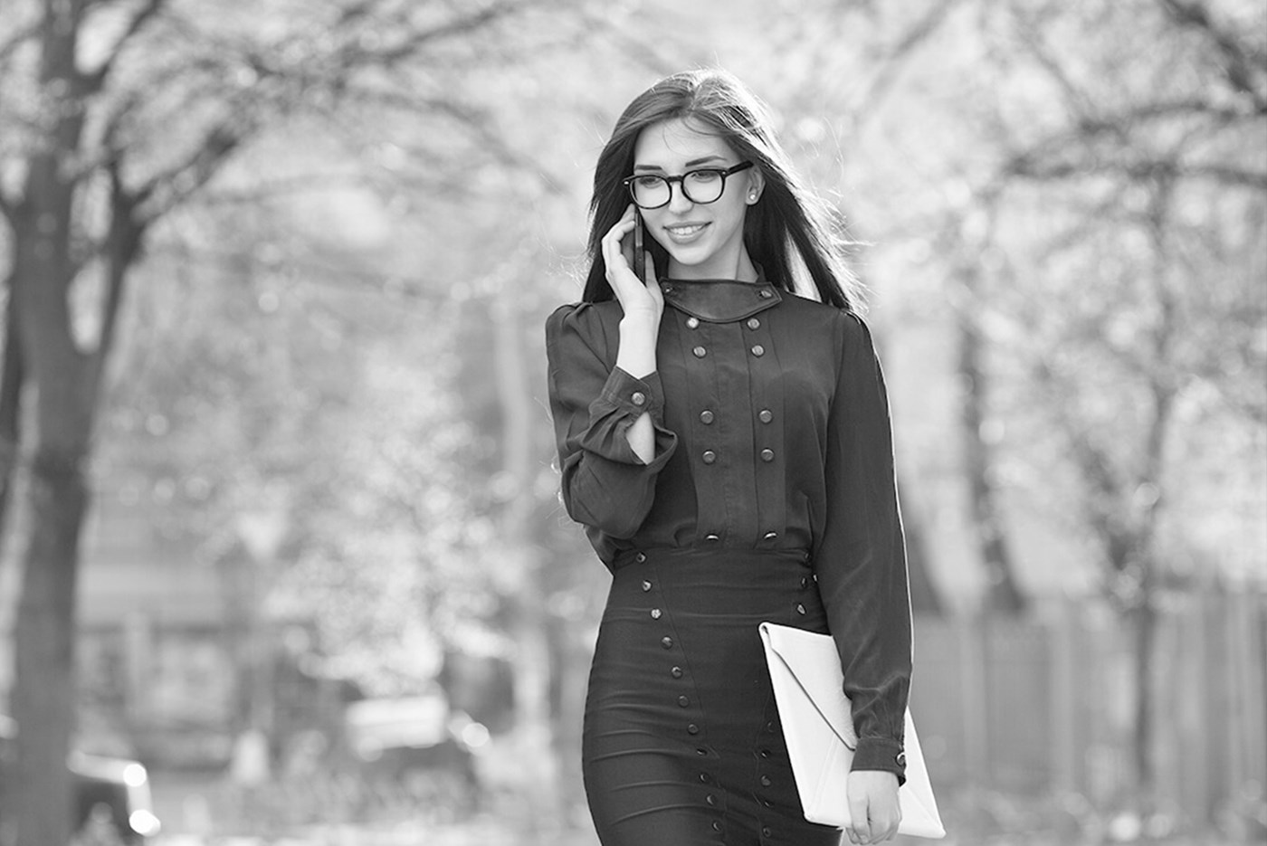 Female walking along park wearing glasses on a phone call