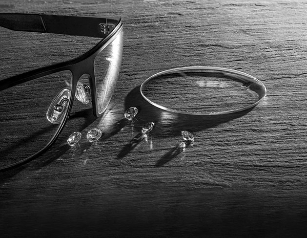 Black and white image of glasses on table with Hoya Vision lenses