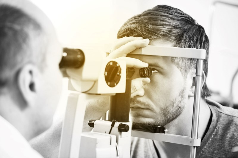 Male having an eye test carried out by a male optician